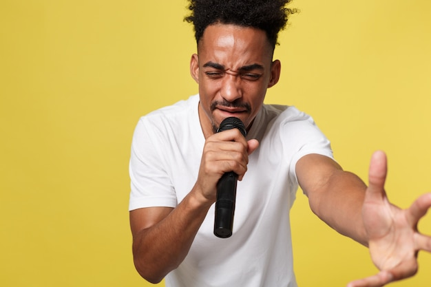 Stylish afro american man singing into microphone isolated on a yellow gold background Premium Photo