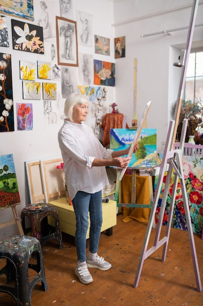 Stylish aged woman. stylish aged woman wearing jeans and sneakers loving painting looking at the picture Premium Photo