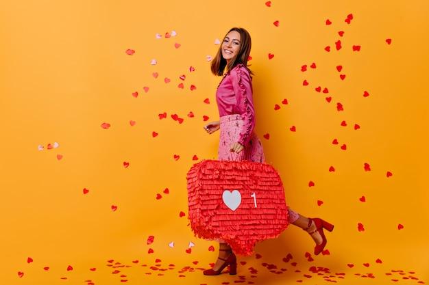 영감을 얻은 미소로 포즈를 취하는 세련된 매력적인 소녀. 색종이 아래 웃고 분홍색 블라우스에 Jocund 여성 블로거. 무료 사진