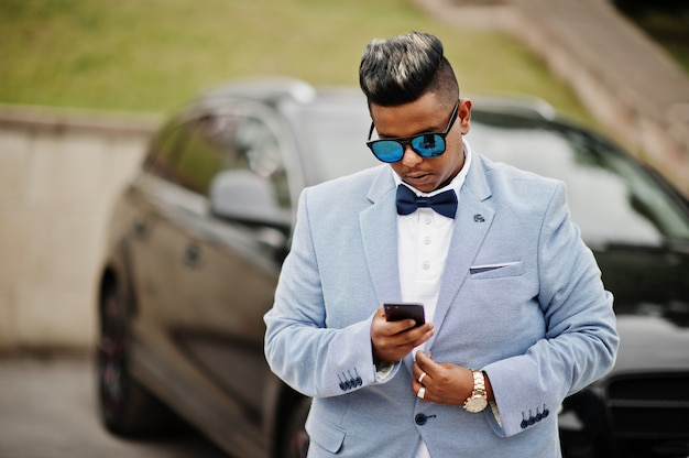 Stylish arabian man in jacket, bow tie and sunglasses against black suv car. arab rich with mobile phone. Premium Photo