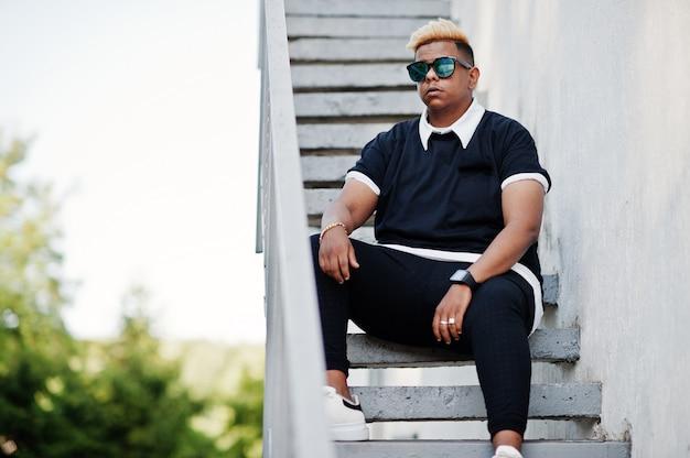 Stylish arabian muslim boy with originally hair and sunglasses posed on streets at ladder. Premium Photo