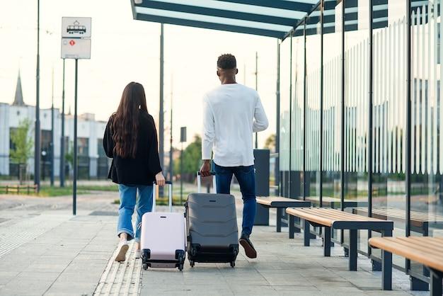 세련된 아시아 소녀와 흑인이 티켓과 함께 여권을 들고 버스 정류장을 걷는 바퀴에 가방을 들고 있습니다. 프리미엄 사진