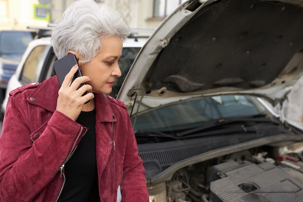 Stylish attractive gray haired mature female driver standing near her broken white car with open hood and talking on the phone Free Photo