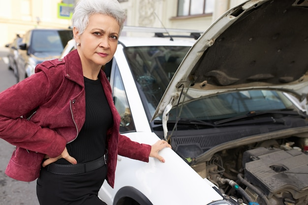 Stylish attractive gray haired mature female driver standing near her broken white car with open hood Free Photo