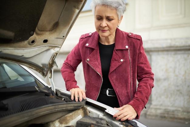 오픈 후드와 함께 그녀의 깨진 흰색 차 근처에 서 세련된 매력적인 회색 머리 성숙한 여성 드라이버 무료 사진