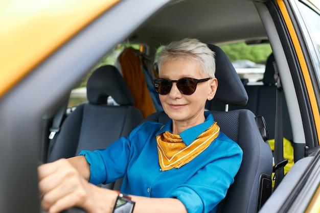 サングラスと腕時計を身に着けて買い物に行く、新しい車を運転する、自信を持って見えるスタイリッシュで魅力的な中年の忙しい女性 無料写真