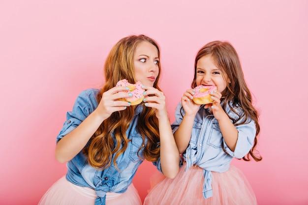 スタイリッシュな魅力的な母親は巻き毛の娘とドーナツを調理し、ピンクの背景にそれらを味わった。ティーパーティーでおいしいお菓子を食べるデニムシャツで美しいお母さんとポーズの少女の肖像画 無料写真