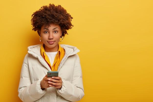 흰색 따뜻한 코트에 세련 된 매력적인 여자, 카메라를 직접보고, 온라인 채팅을 위해 현대 휴대 전화를 사용 하 고, 노란색 배경 위에 절연 곱슬 머리를 가지고 있습니다. 사람과 현대 기술 무료 사진
