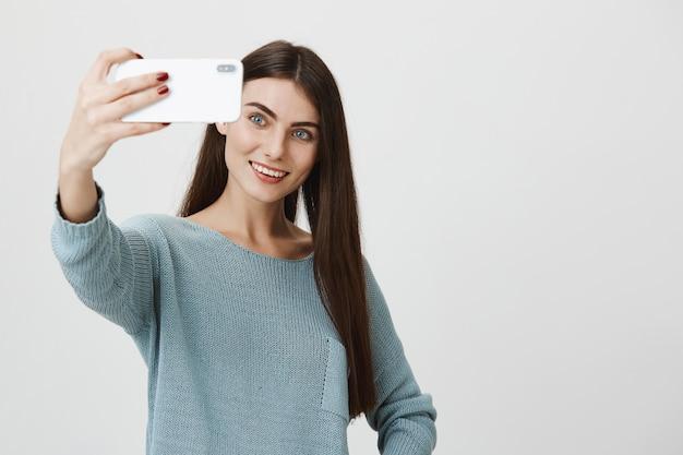 Elegante donna attraente sorridente, prendendo selfie Foto Gratuite