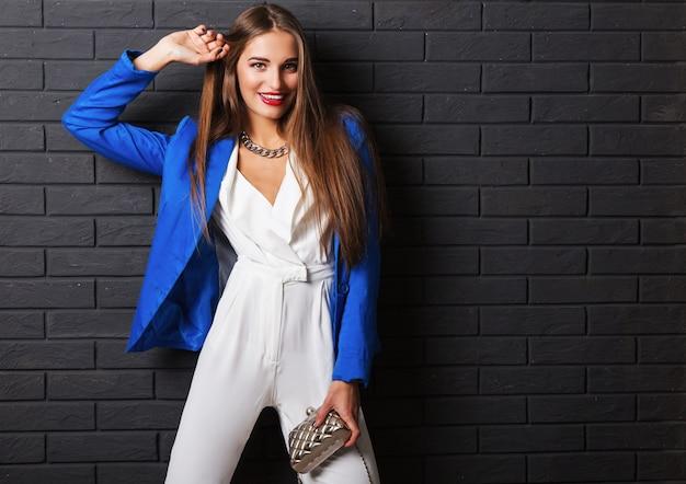 カジュアルな白い衣装と豪華な財布を保持している青いジャケットのスタイリッシュな魅力的な若い女性 無料写真