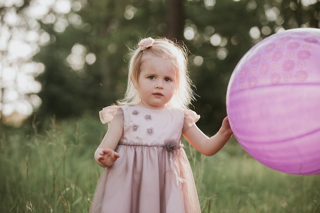 Stylish baby girl 2-5 year old holding big balloon wearing trendy pink dress in meadow. playful. little girl with a balloon in the park Premium Photo