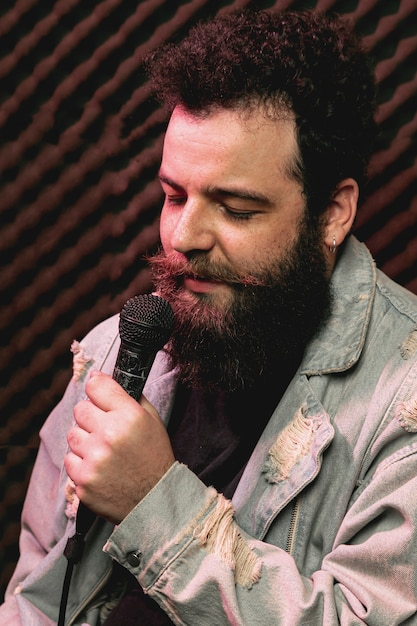 Stylish beard man singing on microphone Free Photo
