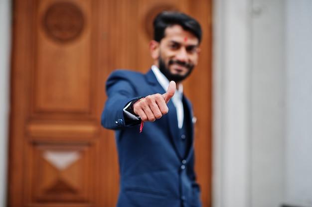 Стильный борода человек с бинди на лбу, носить синий костюм, открытый на улице против двери здания и показать большой палец вверх. Premium Фотографии
