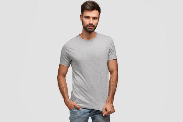 カジュアルなtシャツを着て、ジーンズのポケットに手を入れて、厚い暗い無精ひげを持つスタイリッシュなひげを生やしたハンサムな男 無料写真