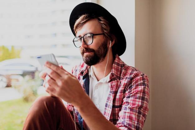 スマートフォンデバイスに新しいモバイルアプリケーションをインストールして音楽を聴く明るい市松模様のシャツを着たスタイリッシュなひげを生やした男。流行に敏感なスタイル。 無料写真