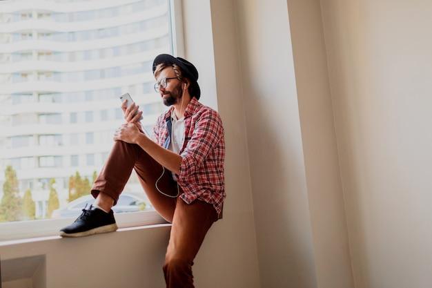 新しいモバイルアプリケーションをインストールする明るい市松模様のシャツを着たスタイリッシュなひげを生やした男 無料写真
