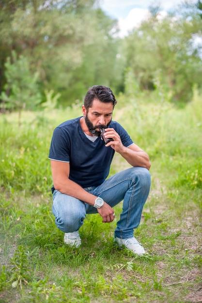 スタイリッシュなあごひげを生やした男は、自然の中で休んでいて、電子タバコから蒸気を吸って放出しています。タバコ以外の喫煙。 Premium写真