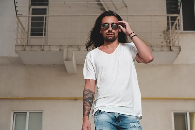 Stylish bearded man model posing with sunglasses Free Photo