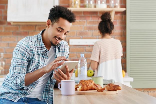Стильный бородатый афроамериканец смешанной расы использует планшетный компьютер, смотрит видео или фильмы онлайн Бесплатные Фотографии