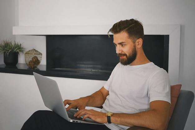 Elegante giovane maschio barbuto rilassante a casa con il computer portatile in grembo, la tastiera mentre messaggistica online con una ragazza interessante tramite il sito di incontri, con un'espressione facciale gioiosa curiosa Foto Gratuite