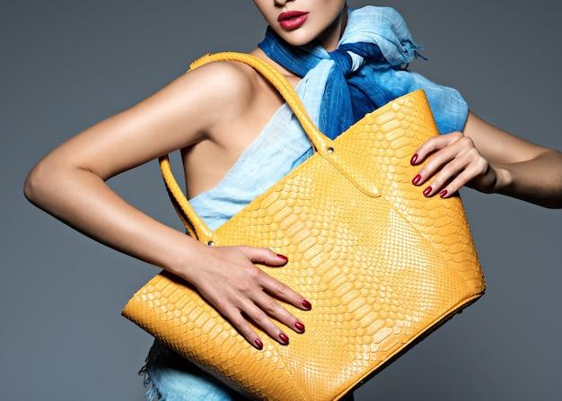 노란색 핸드백과 파란색 스카프를 입고 세련 된 아름 다운 여자. 패션 모델 무료 사진