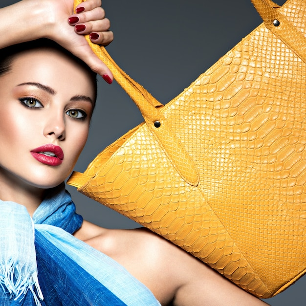 黄色のハンドバッグと青いスカーフを身に着けているスタイリッシュな美しい女性。 無料写真