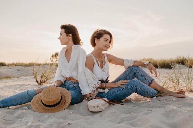 Стильные красивые женщины на летних каникулах на пляже, в богемном стиле, веселятся Бесплатные Фотографии