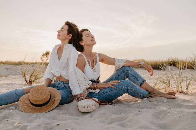 Stylish beautiful women on summer vacation on the beach, bohemian style, having fun Free Photo