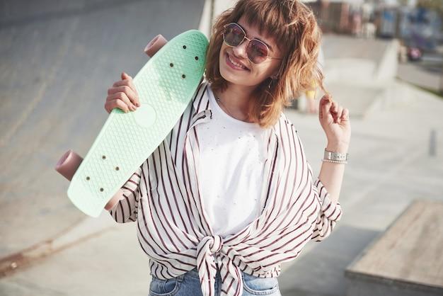 Стильная красивая молодая женщина со скейтбордом, в прекрасный летний солнечный день. Бесплатные Фотографии