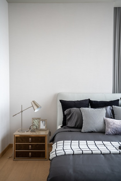 Stylish bedroom corner with leather headboard and bed with soft pillows setting with white painted wall on the background / cozy interior design / modern interior Premium Photo