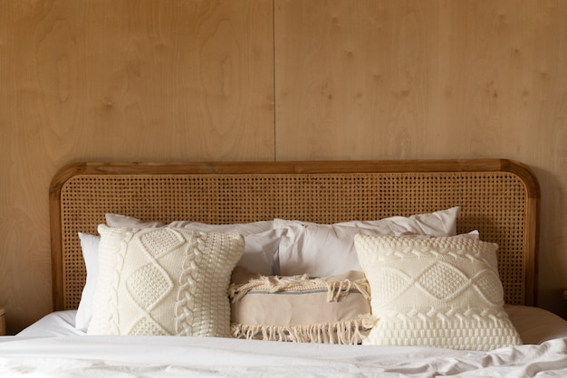 Stylish bedroom corner with rattan headboard bed and soft pillow decoration with plywood wall  cozy interior design  copy space Premium Photo