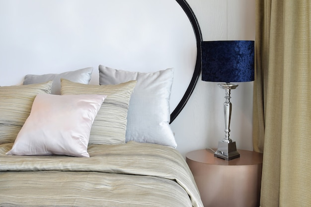 Stylish bedroom interior design with pillows on bed and decorative table lamp. Premium Photo