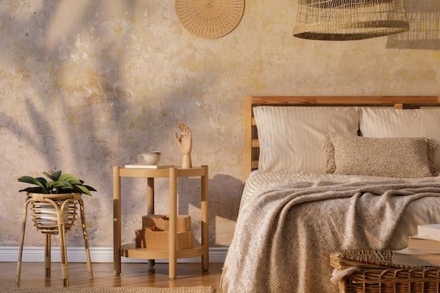 Stylowe wnętrze sypialni z designerskim stolikiem kawowym, meblami, roślinami, dywanem, dekoracją z rattanu i eleganckimi akcesoriami osobistymi.  piękne beżowe prześcieradła, koc i poduszki.  Zdjęcie premium