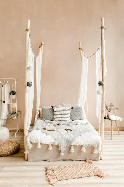 Стильная спальня бежевого цвета с кроватью с постельным бельем в стиле бохо Premium Фотографии