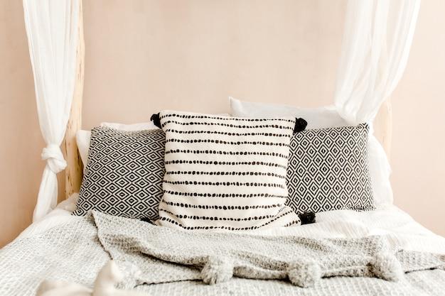 Стильная спальня бежевого цвета с кроватью с постельным бельем, подушками в стиле бохо Premium Фотографии
