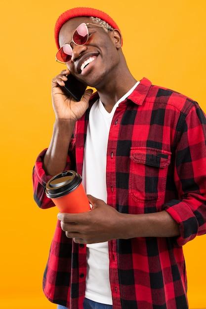 市松模様の赤いシャツで美しい笑顔でスタイリッシュな黒人アメリカ人が彼の手で黄色のスタジオの背景にコーヒーのガラスを保持しています。 Premium写真