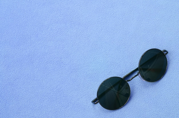 0c1419afd062 Stylish black sunglasses with round glasses lies on a blanket made of soft  and fluffy light blue fleece fabric. Premium Photo