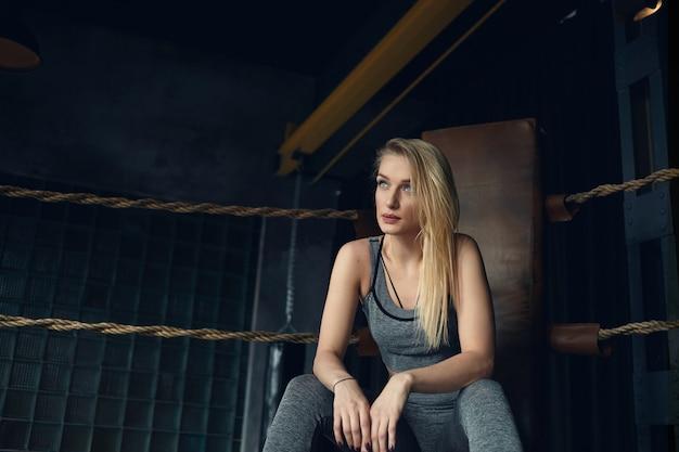 Elegante ragazza bionda ventenne che si siede sulla sedia in pelle nell'angolo del ring di pugilato Foto Gratuite