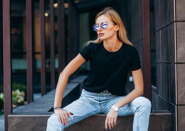 Stylish blonde girl wearing black t-shirt and glasses posing against street Premium Photo