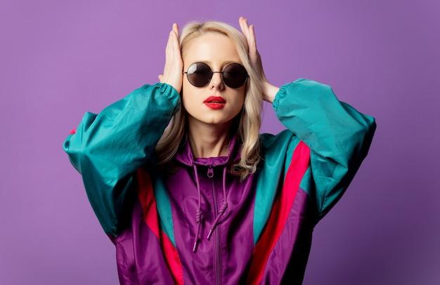 Стильная блондинка в ветровке 80-х и круглых солнцезащитных очках на фиолетовой стене Premium Фотографии