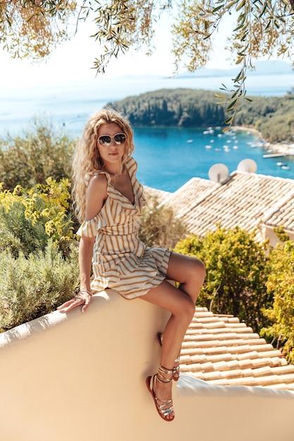 Стильная блондинка наслаждается летним отдыхом у моря Premium Фотографии