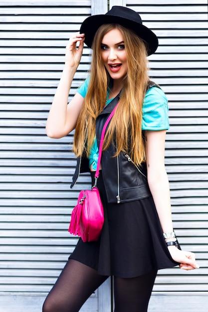 Elegante donna bionda in posa per strada, indossa un abito luminoso hipster, giocose emozioni fresche, divertimento, divertimento, felice vacanza da solo, cappello vintage e minigonna. Foto Gratuite