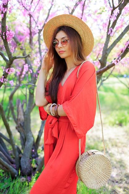 Elegante ragazza bohémien in posa in abito di corallo e cappello di paglia vicino al ciliegio in fiore nel parco di primavera. Foto Gratuite