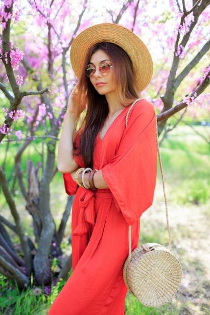 Стильная богемная девушка позирует в коралловом платье и соломенной шляпе возле цветущей вишни в весеннем парке. Бесплатные Фотографии