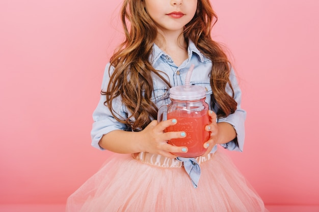 Stylish brightful image of cute little girl with long brunette hair, in tulle skirt holding glass with juice isolated on pink background. happy childhood with lovely drink, tasty young years Free Photo
