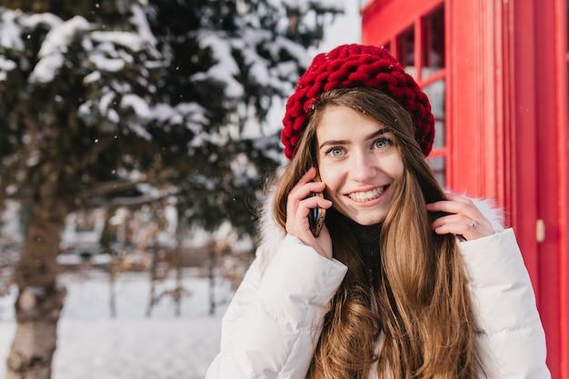 雪だらけの通りに電話で話している赤い帽子の長いブルネットの髪を持つ素晴らしい若い女性のスタイリッシュなイギリスの肖像画。寒い冬を楽しんで、元気な気分。テキストのための場所。 無料写真