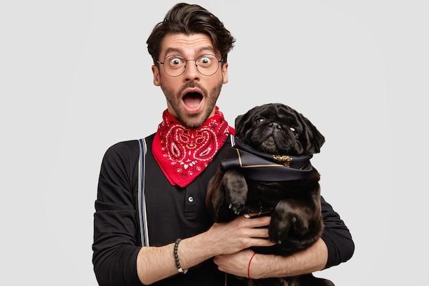 Stylish brunet man wearing red bandana holding dog Free Photo