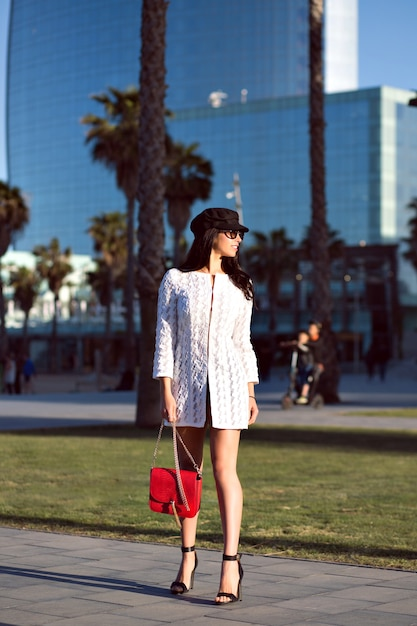 Stylish brunette woman walking , fancy luxury style outfit, modern buildings and palms, toned colors. Free Photo