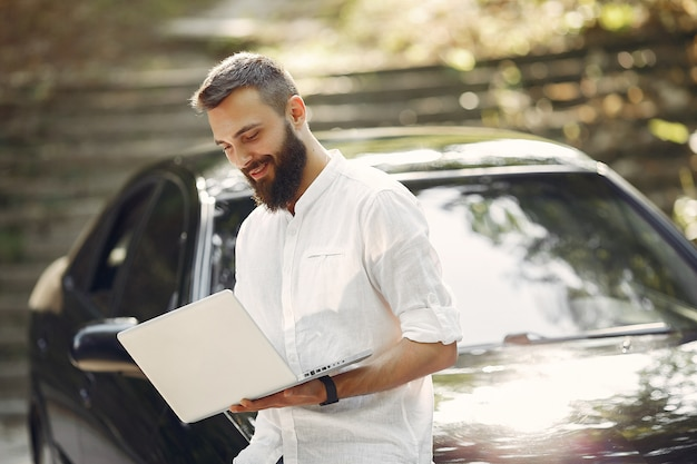 Stylish businessman standing near the car and use the laptop Free Photo