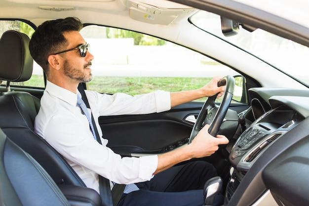 Стильный бизнесмен в темных очках за рулем автомобиля Premium Фотографии